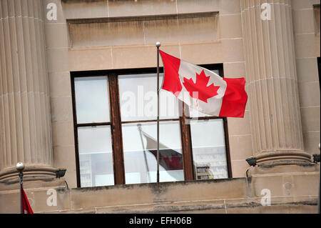 The Canadian flag on a flagpole on the side of a building in London, Ontario, Canada. - Stock Photo