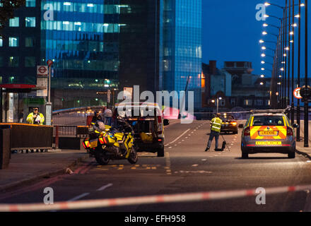 Metropolitan Police officers on the London Bridge investigate the aftermath of a collision in which a cyclist was - Stock Photo
