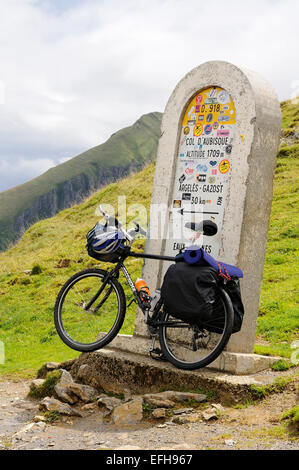 A sign post on Col d'Aubisque (1709m), Pyrenees, (France) with a bicycle leaning. - Stock Photo