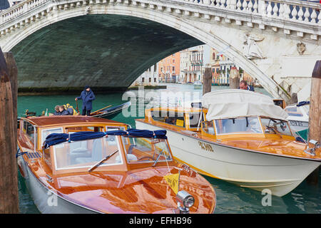 Water taxis by the Rialto Bridge Venice Veneto Italy Europe - Stock Photo