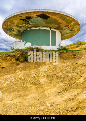 An abandoned concrete structure that resembles a flying saucer is covered with paint splotches where graffiti once - Stock Photo