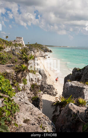 Walking the Tulum Ruins Beach. A couple walks alone along the beach that will soon be crowded with bathers, sun and water.