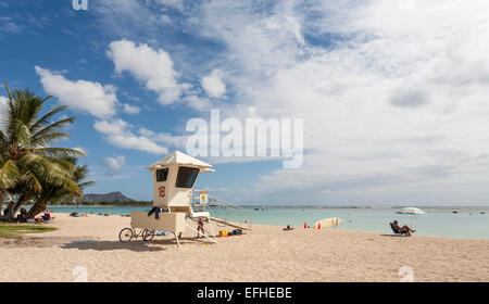 Lifeguard Station on Ala Moana Beach Honolulu. White sand, a blue sky and lounging sunbathers set the scene - Stock Photo