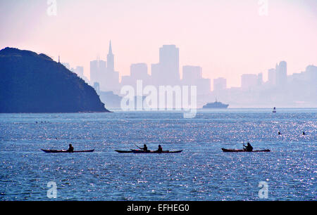 kayakers paddle on San Francisco Bay in Tiburon Caliofornia with angel island and the skyline of San Francisco in - Stock Photo