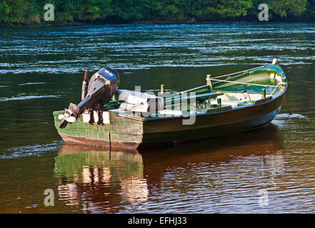 Small fishing boat anchored and reflected in loch long at for Green boat and motor