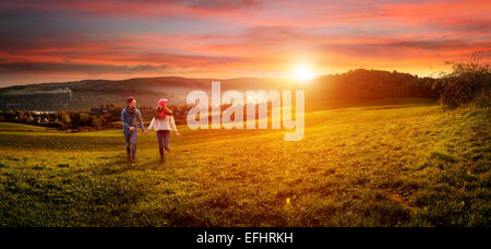 Loving couple holding hands running on the field. beautiful landscape - Stock Photo