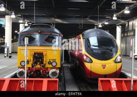 Class 57 diesel locomotive and class 390 electric multiple unit (Pendolino) train in London Euston railway station. - Stock Photo