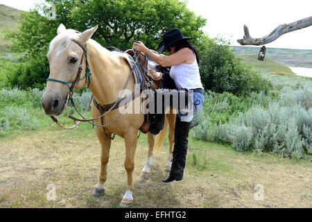 Woman climbs onto her horse, La Reata Ranch, Saskatchewan, Canada. - Stock Photo