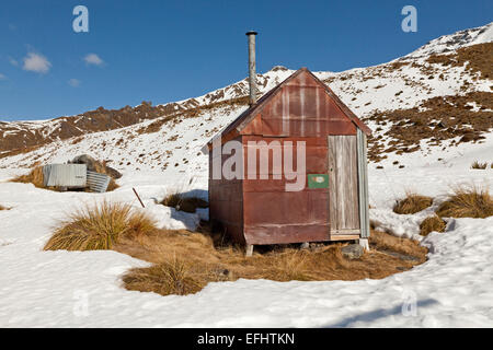 Historical, gold miner's iron hut in snow, pioneers hut in the mountains, near Queenstown, South Island, New Zealand - Stock Photo