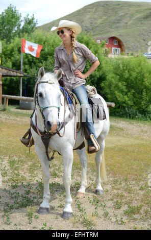 Woman on horseback, La Reata Ranch, Saskatchewan, Canada. - Stock Photo
