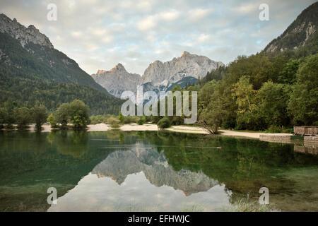 Jasna Lake with mountains in backdrop, Kranjska Gora, Julian Alps, Gorenjska, Slovenia - Stock Photo