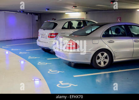 Cars parked on disabled reserved spaces in underground parking lot France - Stock Photo