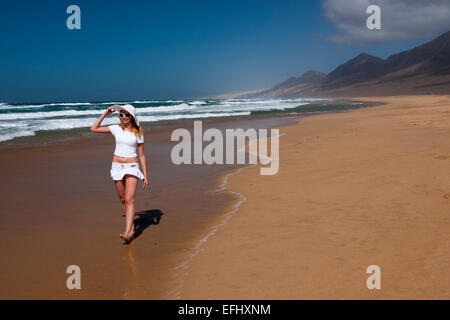 Young woman walking along the beach, Nature Reserve, Jandia, Fuerteventura, Canary Islands, Spain, Europe - Stock Photo