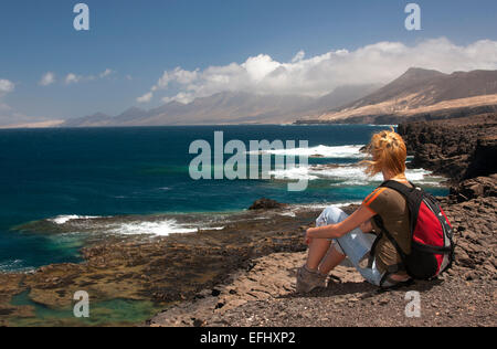 Woman sitting on rocks, looking out to sea, Nature Reserve, Jandia, Fuerteventura, Canary Islands, Spain, Europe - Stock Photo