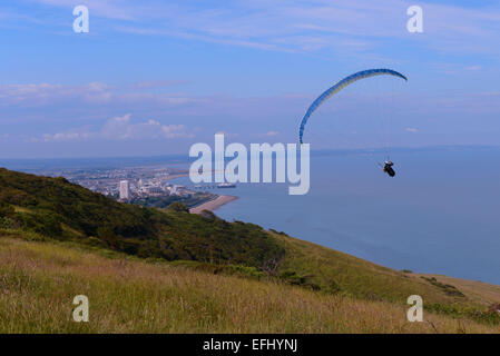 Paraglider flying off Beachy Head towards Eastbourne - Stock Photo
