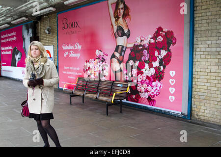 London, UK. 5th February, 2015. A commuter stands on  the platform at  Putney Bridge Station in front of a giant - Stock Photo