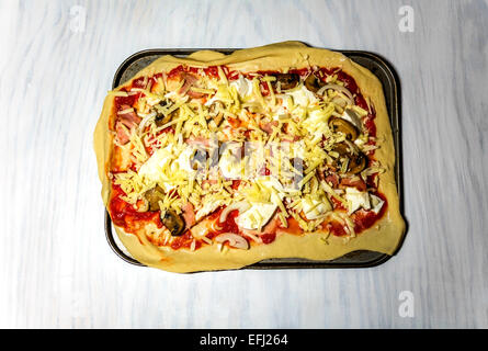A home made pizza with lots of topping, ready for the oven. - Stock Photo