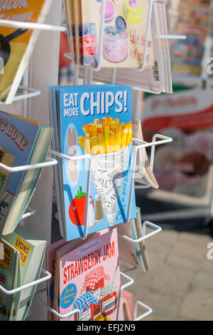 BRIGHTON, UK- JULY 28: Eat more chips postcard in a postcard rack on the seafront in Brighton, july 2013. - Stock Photo