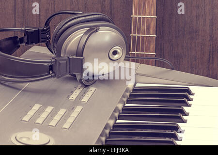 Digital midi keyboard, headphones and acoustic guitar in the studio. - Stock Photo