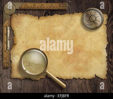 vintage nautical compass and loupe on table with treasure map - Stock Photo