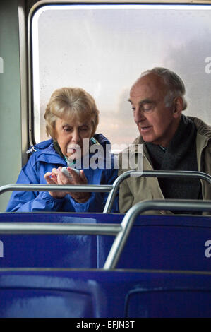 Vertical portrait of an elderly couple sitting together on a bus using a smartphone. - Stock Photo