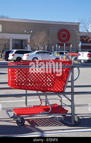 Single red shopping buggy in cart rack in front of Target department store. - Stock Photo