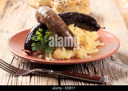 Pan roasted sausages with sauerkraut and potatoes - Stock Photo