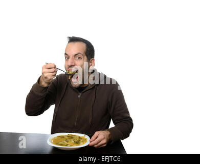 Young man eating vegetable soup with his mouth wide open - Stock Photo
