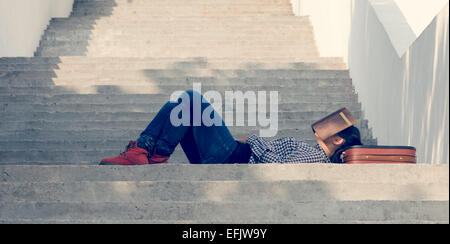 Sleeping girl on the stairs with book - Stock Photo