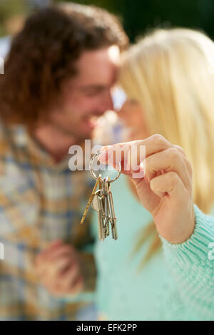 First time buyers holding keys to new house - Stock Photo