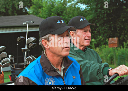 US President George W. Bush sits in a golf cart with his father former President George H.W. Bush wearing caps with - Stock Photo