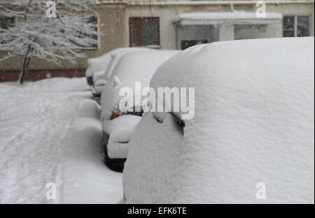 Snow day. Cars covered in snow in the outdoors near house. - Stock Photo