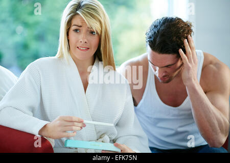 Unhappy couple finding out she is pregnant - Stock Photo