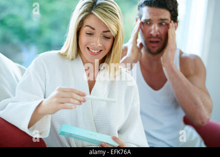Happy girl finding out she is pregnant with upset man in background