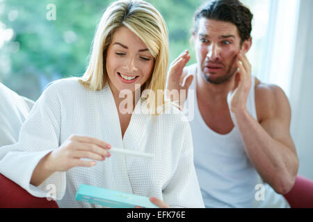Happy girl finding out she is pregnant with upset man in background - Stock Photo