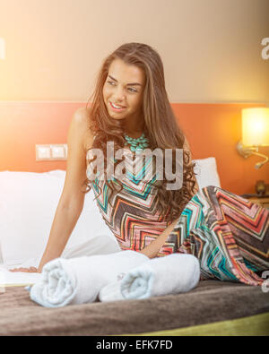 Young woman sitting in the bed of a hotel room - Stock Photo