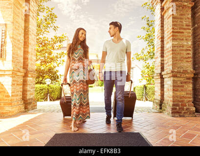 Young couple standing at hotel corridor upon arrival, looking for room, holding suitcases - Stock Photo