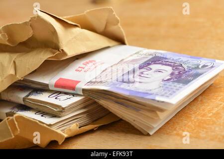 Twenty pound notes in a brown envelope - Stock Photo