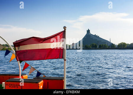 The national flag of Latvia on the ship on the background of the National Library in Riga - Stock Photo