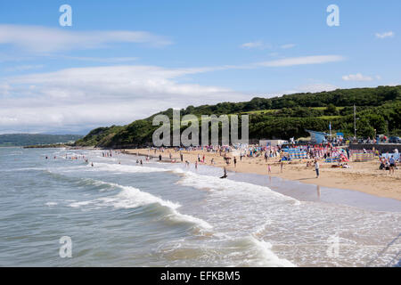 Holidaymakers on safe sandy beach traeth at high tide in summer. Benllech, Isle of Anglesey (Ynys Mon), North Wales, - Stock Photo