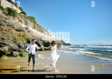happy couple holding hands running on the beach near sea in wedding day - Stock Photo