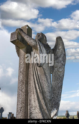 Angel statue embracing a cross and celtic graveyard  in Ardmore county Waterford, Ireland with added grain - Stock Photo