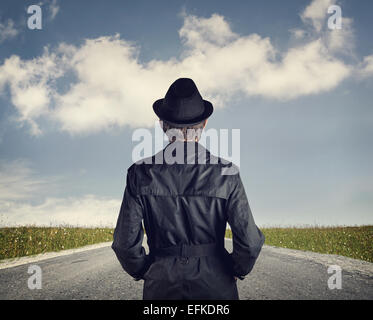 Man in black hat on the road at blue cloudy sky background - Stock Photo