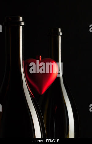 Silhouettes of elegant wine bottles with red heart on a black background - Stock Photo