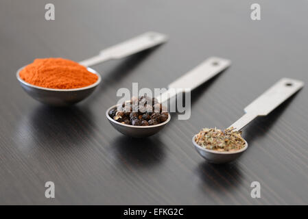 Peppercorns, Paprika and thyme in measuring spoons on a dark wooden surface - Stock Photo