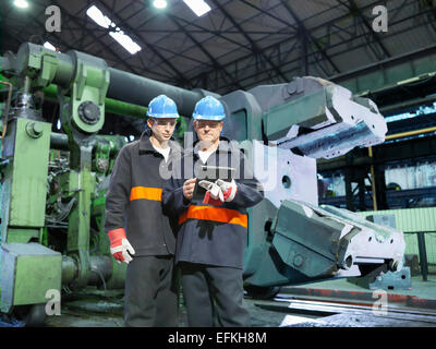 Steelworkers with digital tablet in front of forge in steelworks - Stock Photo