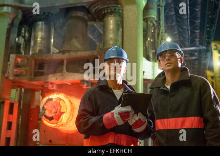 Steelworkers using digital tablet in front of 10,000 tonne forging press in steelworks - Stock Photo