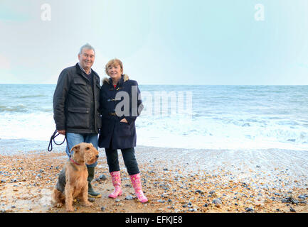 Portrait of senior couple with dog on beach - Stock Photo