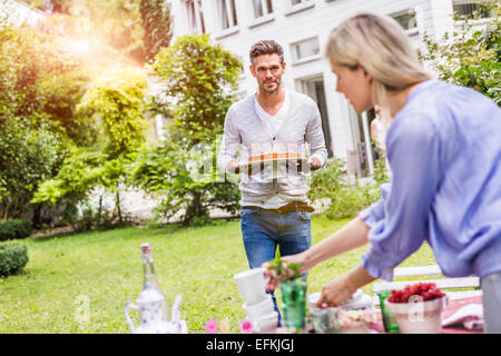 Mid adult man carrying cake on cake stand, walking towards garden table - Stock Photo