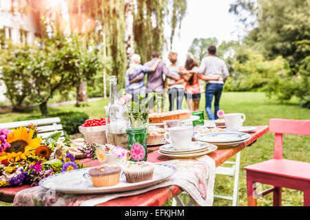 Group of friends walking away with arms around each other, garden party table with food in foreground - Stock Photo